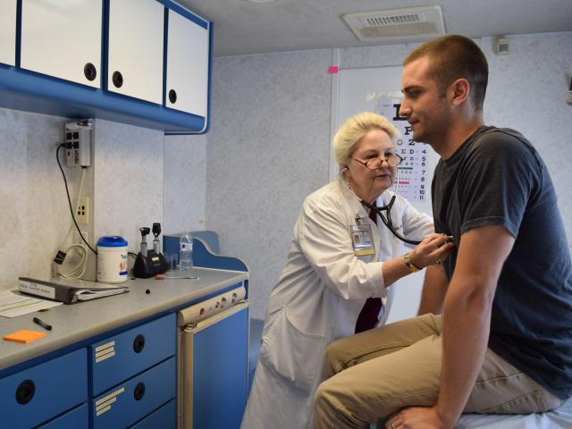 Doctor checks patient's heart rate with a stethoscope