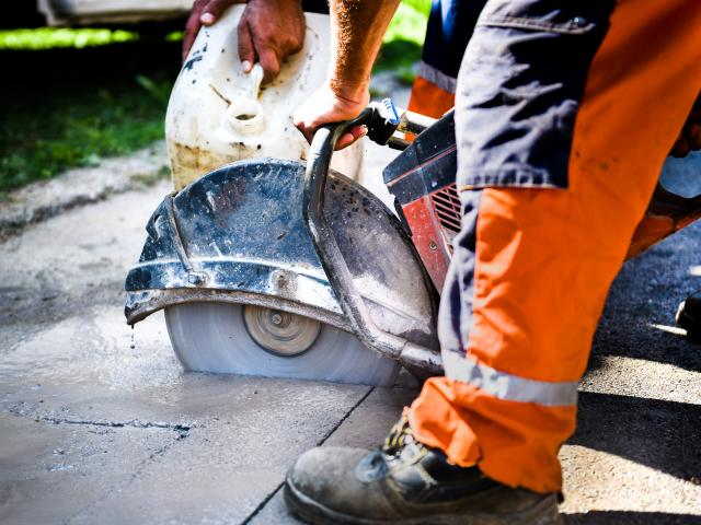 close up man cutting concrete with large circular saw