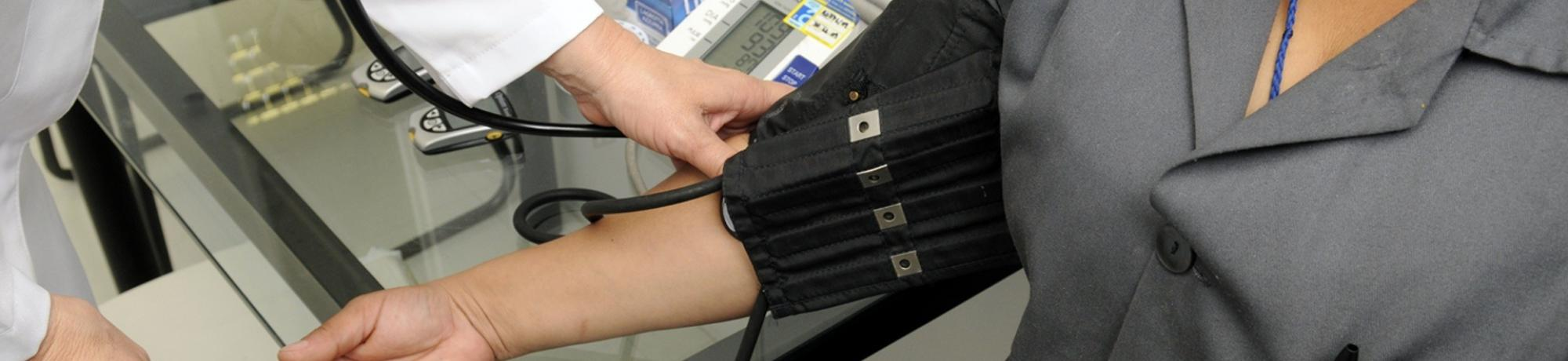 Doctor checking patient's blood pressure with cuff